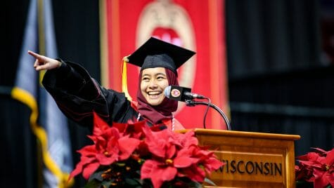 """UW–Madison graduate and student speaker Lisa Kamal points to an audience member during her speech at the winter commencement ceremony Dec. 15, 2019, at the Kohl Center. Videos of her speech have been viewed more than 3.5 million times. Looking back, Lisa calls the experience life-changing. """"It made me realize how much of an impact we can make no matter how small we feel,"""" she says."""