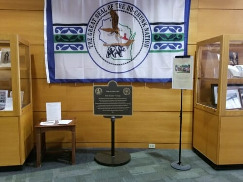 Photo: Plaque in front of Ho-Chunk Nation flag, flanked by display cases