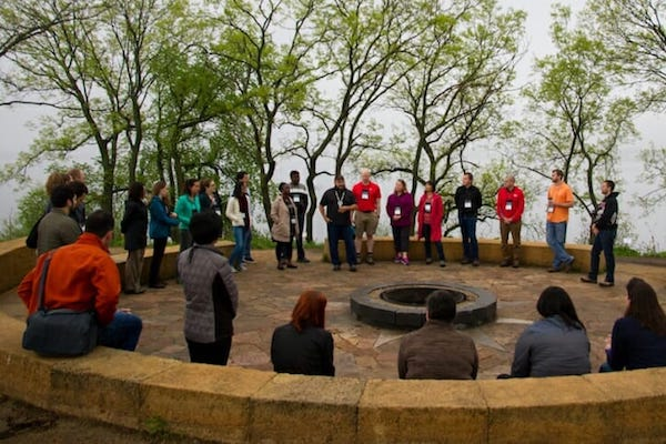 Photo: People standing in front of trees with lake in background and story circle and fire pit in foreground