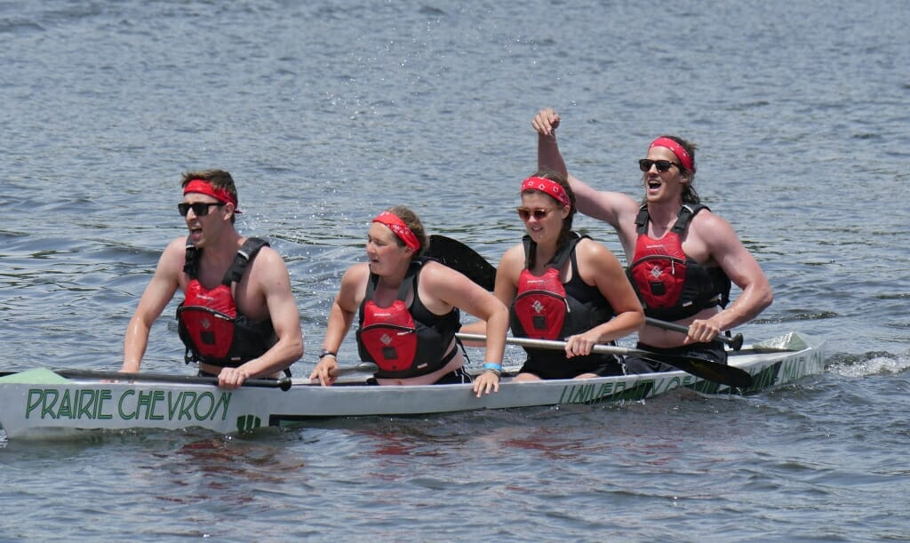 """Photo: 4 people in life vests and red headbands rowing a concrete canoe named """"Prairie Chevron"""" on a lake"""