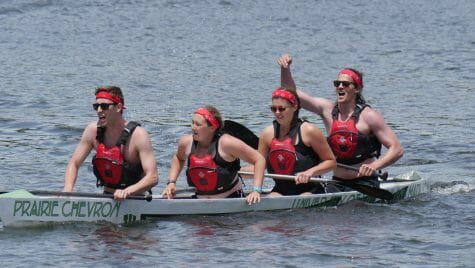 Photo: 4 people in life vests and red headbands rowing a concrete canoe named