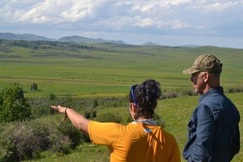 Two people talk in an open field.