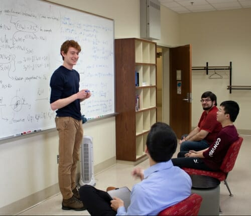 Photo: Student standing in front of whiteboard with equation on it