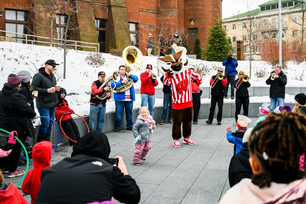 Bucky Badger dances with a child, with a band in the background.