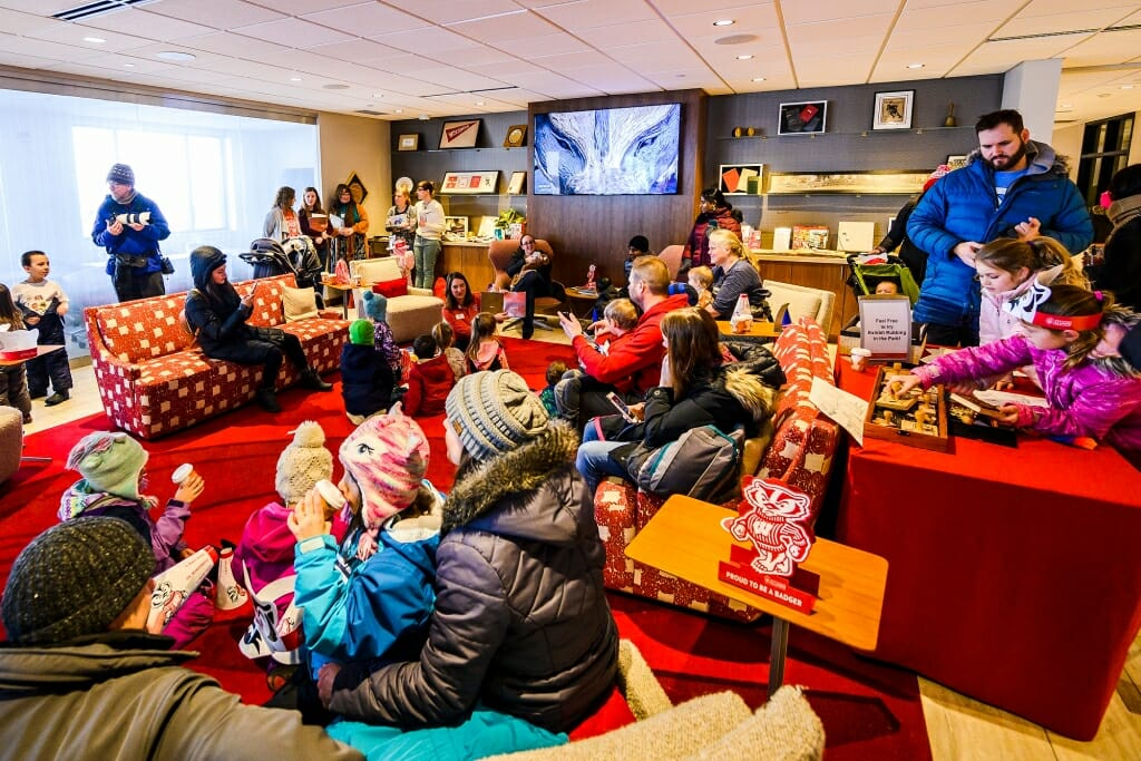 A crowded room at the Alumni Center, with a TV on and many sipping hot chocolate.