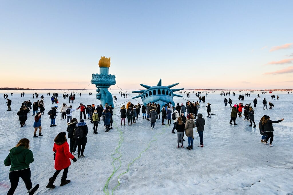 People flock around an inflatable Statue of Liberty head on the ice and take photos.