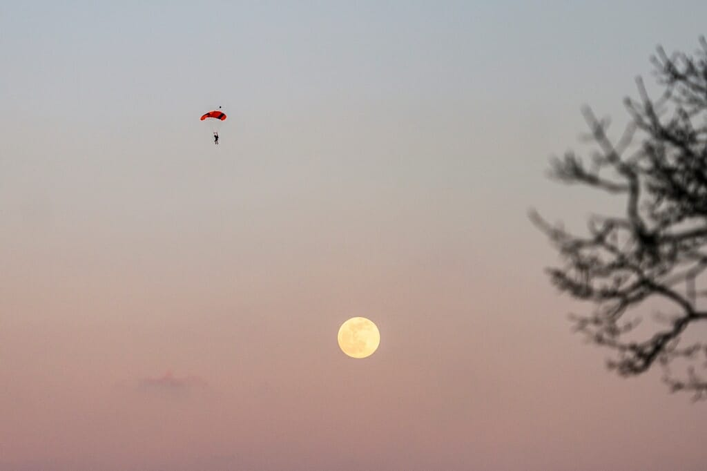 A sky diver floats by the moon.