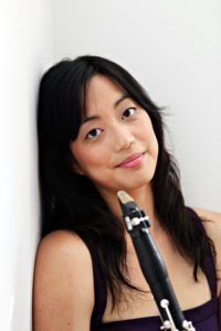 Portrait of Alicia Lee leaning against a wall and holding a clarinet