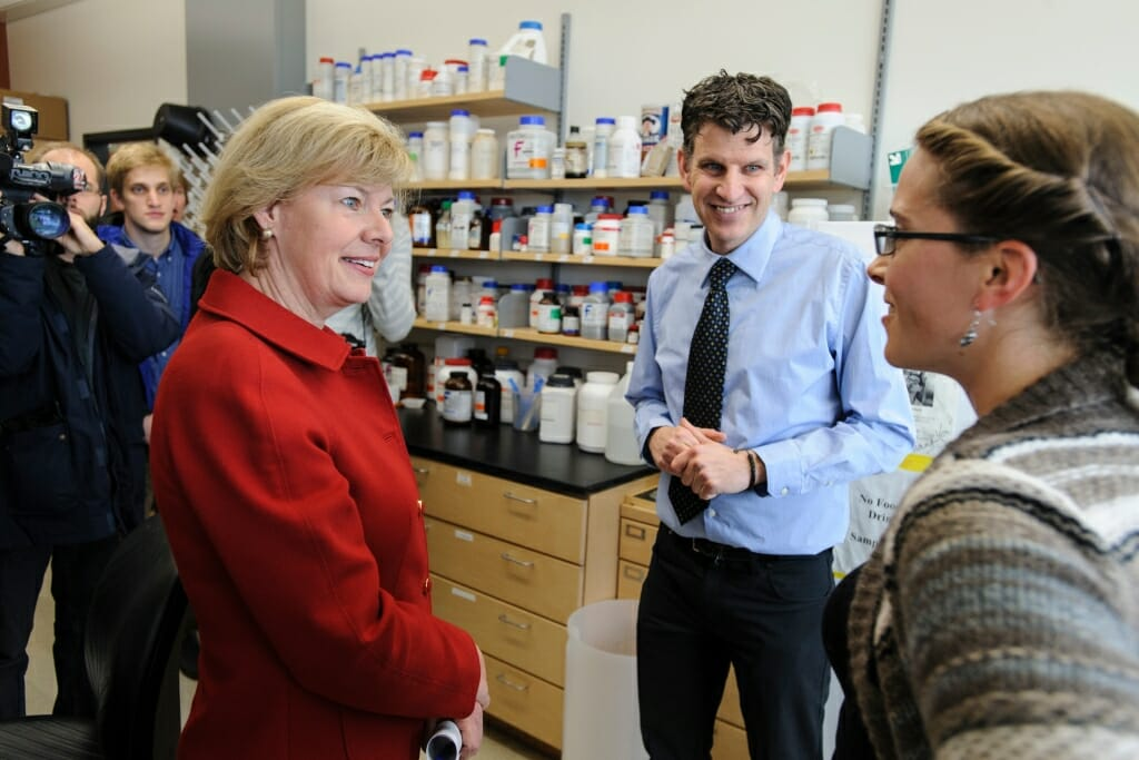 The senator and a man talk in a lab full of scientific equipment.