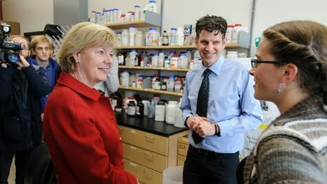 The senator listens to lab member in a lab full of scientific equipment.