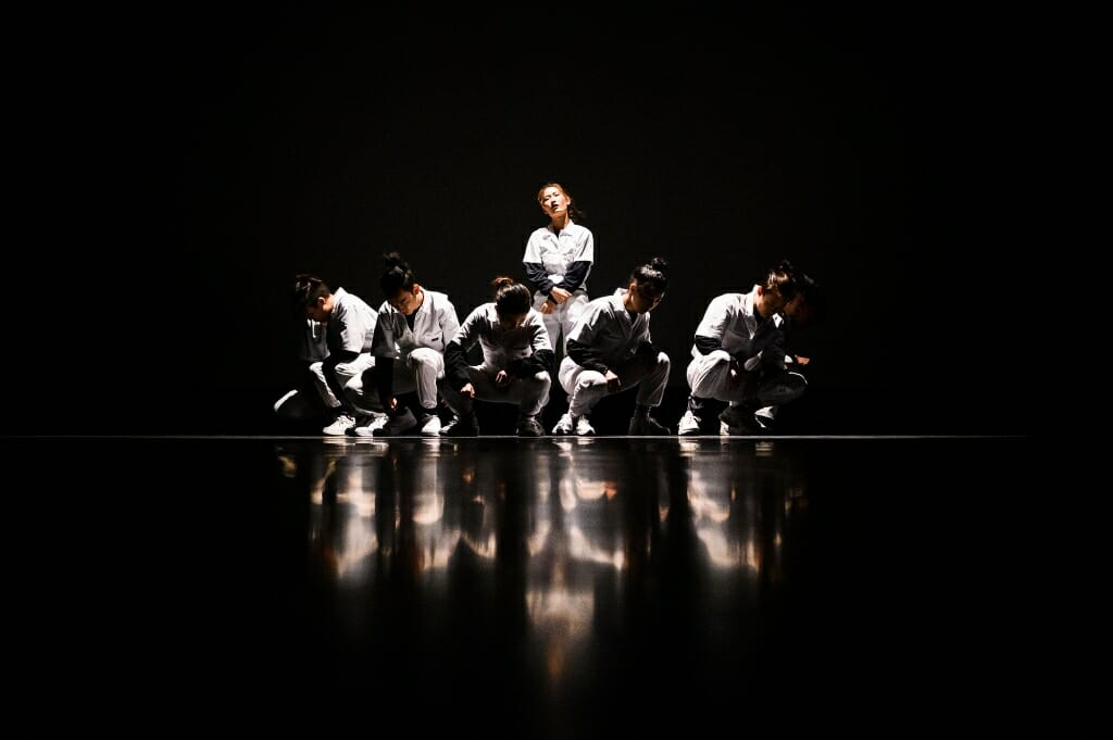 Several crouching dancers form a circle around another dancer.