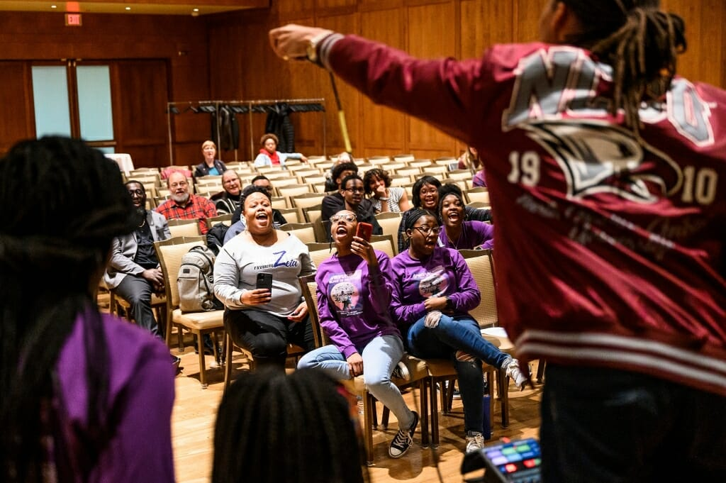 From left to right, audience members Karla Foster, Jaylah Batemon and Karinton DeVille cheer as Freelon leads a freestyle beat-making session during his Black History Month event talk.