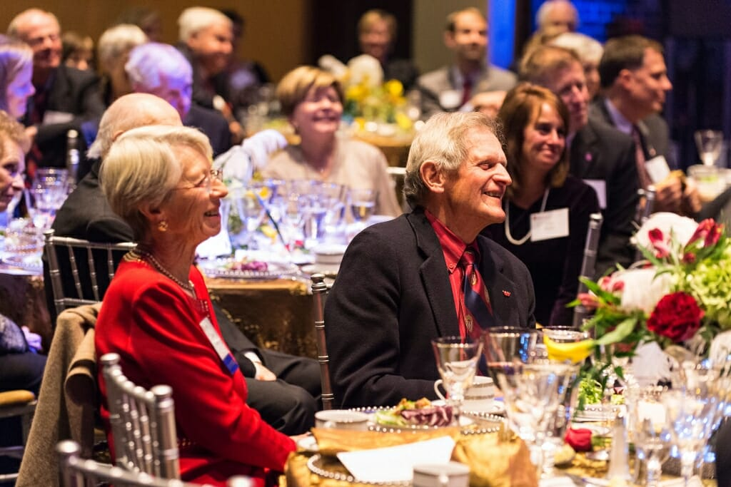 Tashia and John Morgridge sitting at a table smiling among other tables surrounded by people applauding