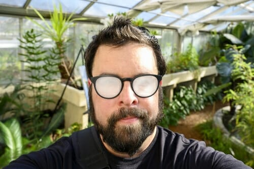 Bryce inside the greenhouse in front of green plants with his eyeglasses fogged over