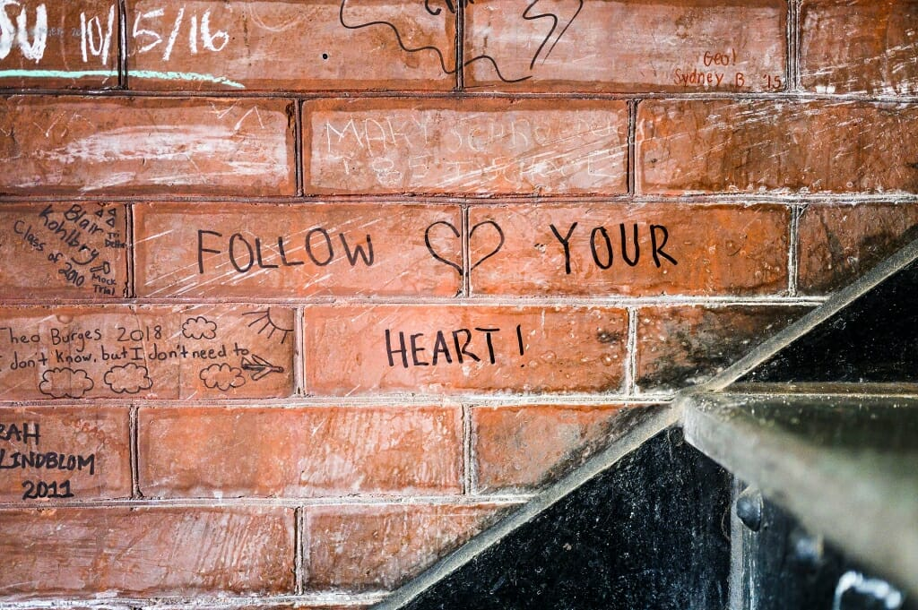 A brick wall has a heart sketched and the words