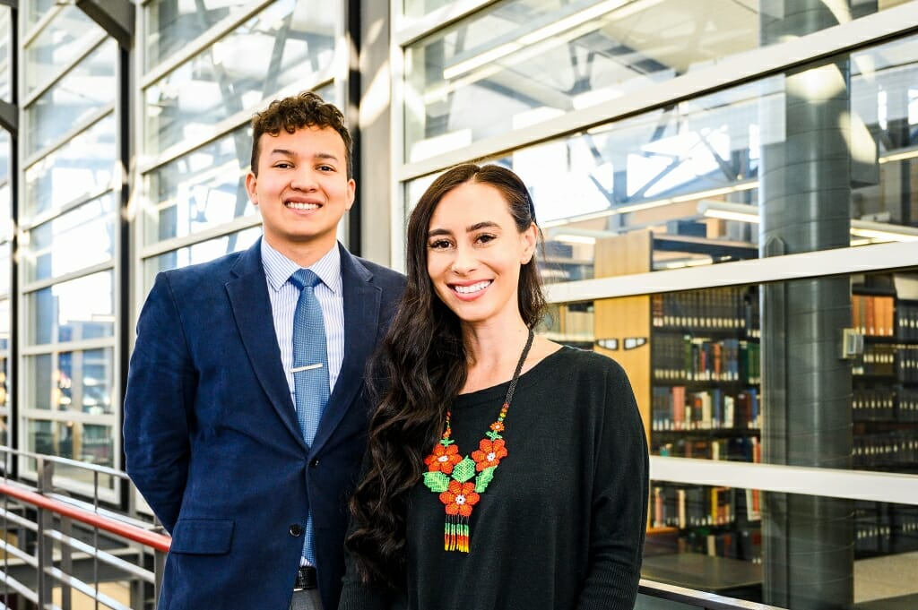 Portrait of Lorenzo Gudino and Catelin Aiwohi standing in the atrium of the law school with book shelves in background