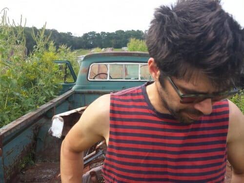 Pinc standing behind a green pickup truck, looking down through sunglasses