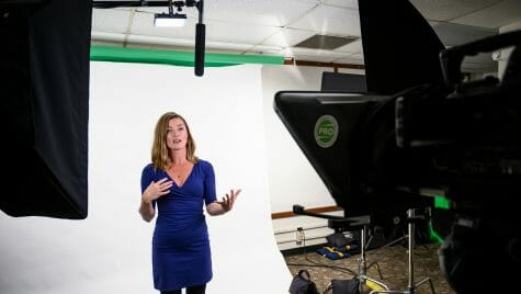 Sara McKinnon standing in front of a white background, speaking into a video camera