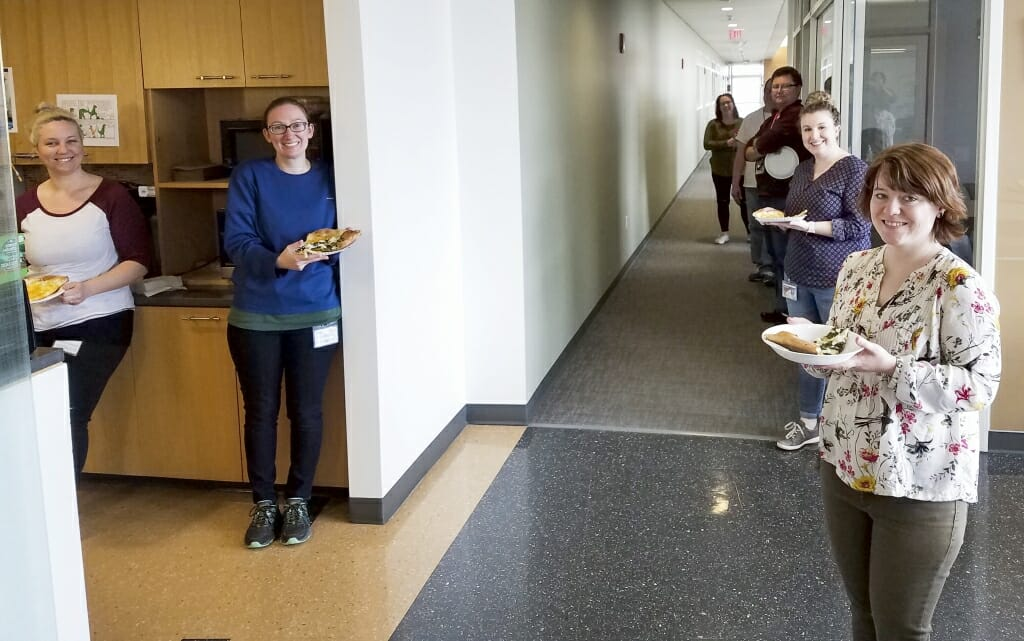 Employees at the Wisconsin State Laboratory of Hygiene take a break to enjoy pizza. The lab has conducted extensive testing for COVID-19, and employees have continued to report to work.