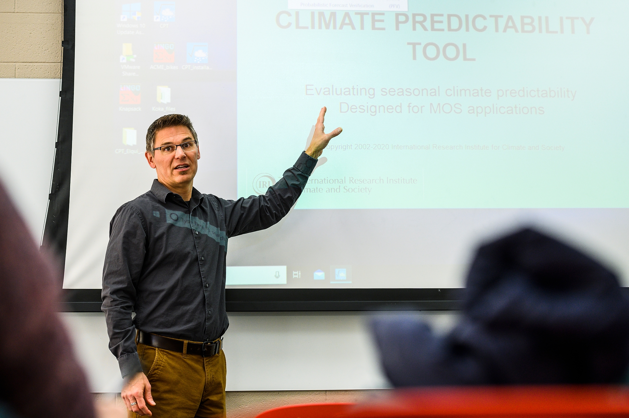 "Paul Block gesturing toward a large screen with the words ""CLIMATE PREDICTABILITY TOOL"" projected on it"