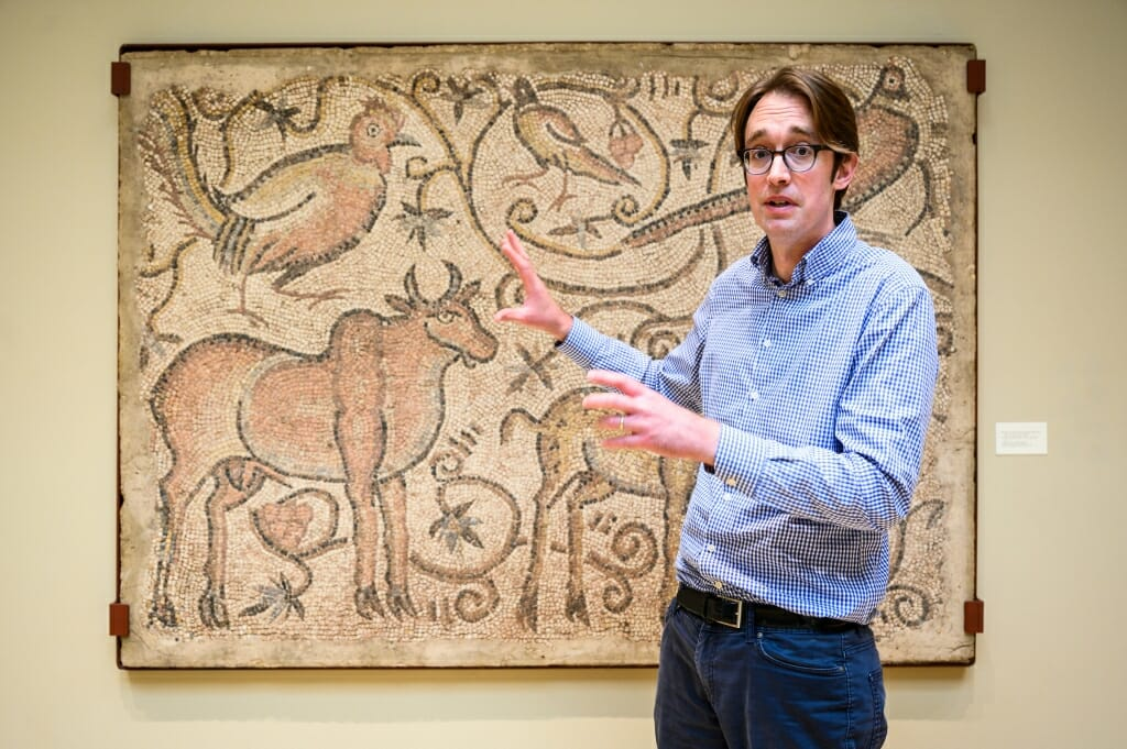 William Brockliss motioning toward a mosaic showing a bull and several birds
