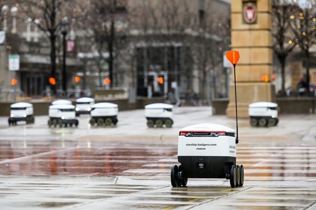 Several food robots roll along a rainy walkway.