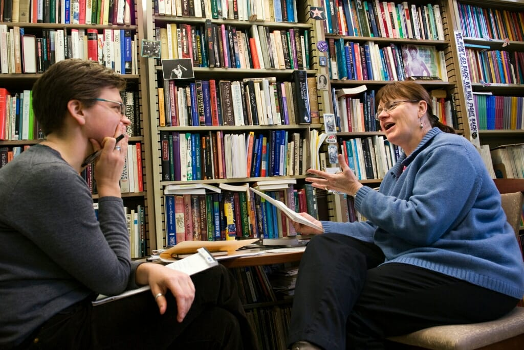 Susan Cook and Jessica Courtier conversing in front of a wall of shelves filled with books