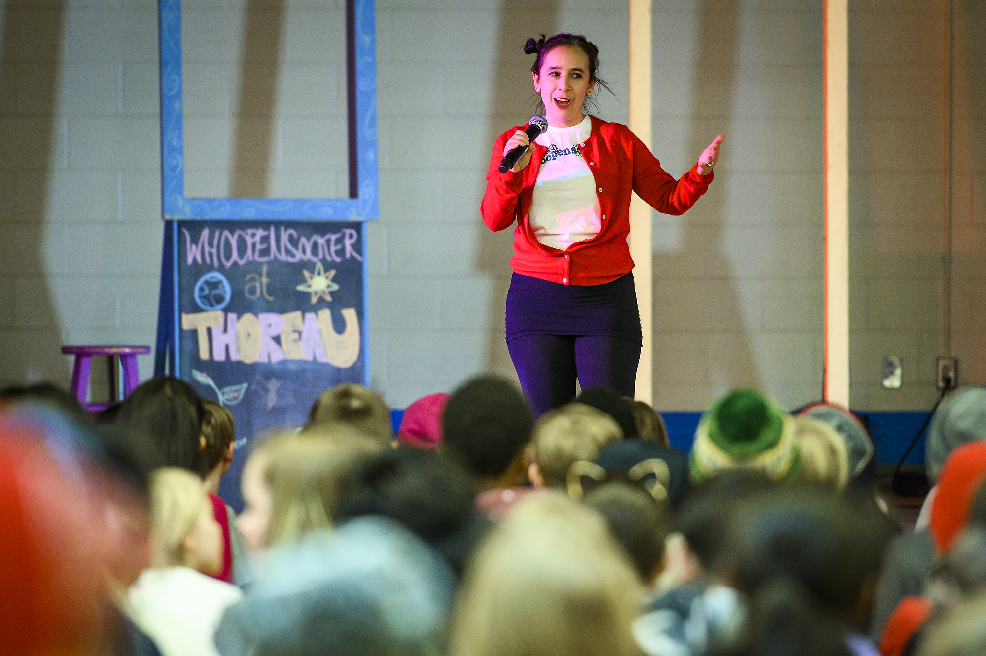 Erica Halverson speaking into a handheld microphone in front of a crowd of children