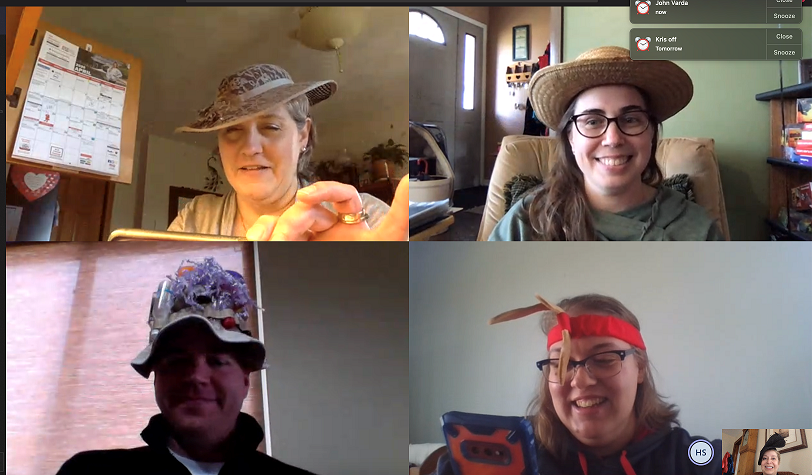 Four people wearing hats in a video chat