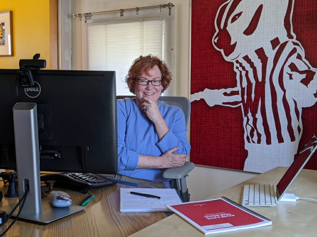Linda Zwicker sitting opposite her computer on a desk with picture of Bucky Badger on wall behind her