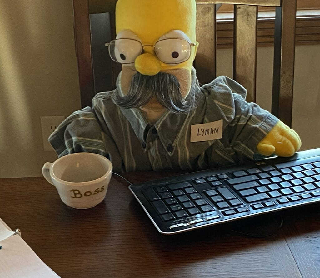 Homer Simpson figure posed at a keyboard with a mug that says Boss