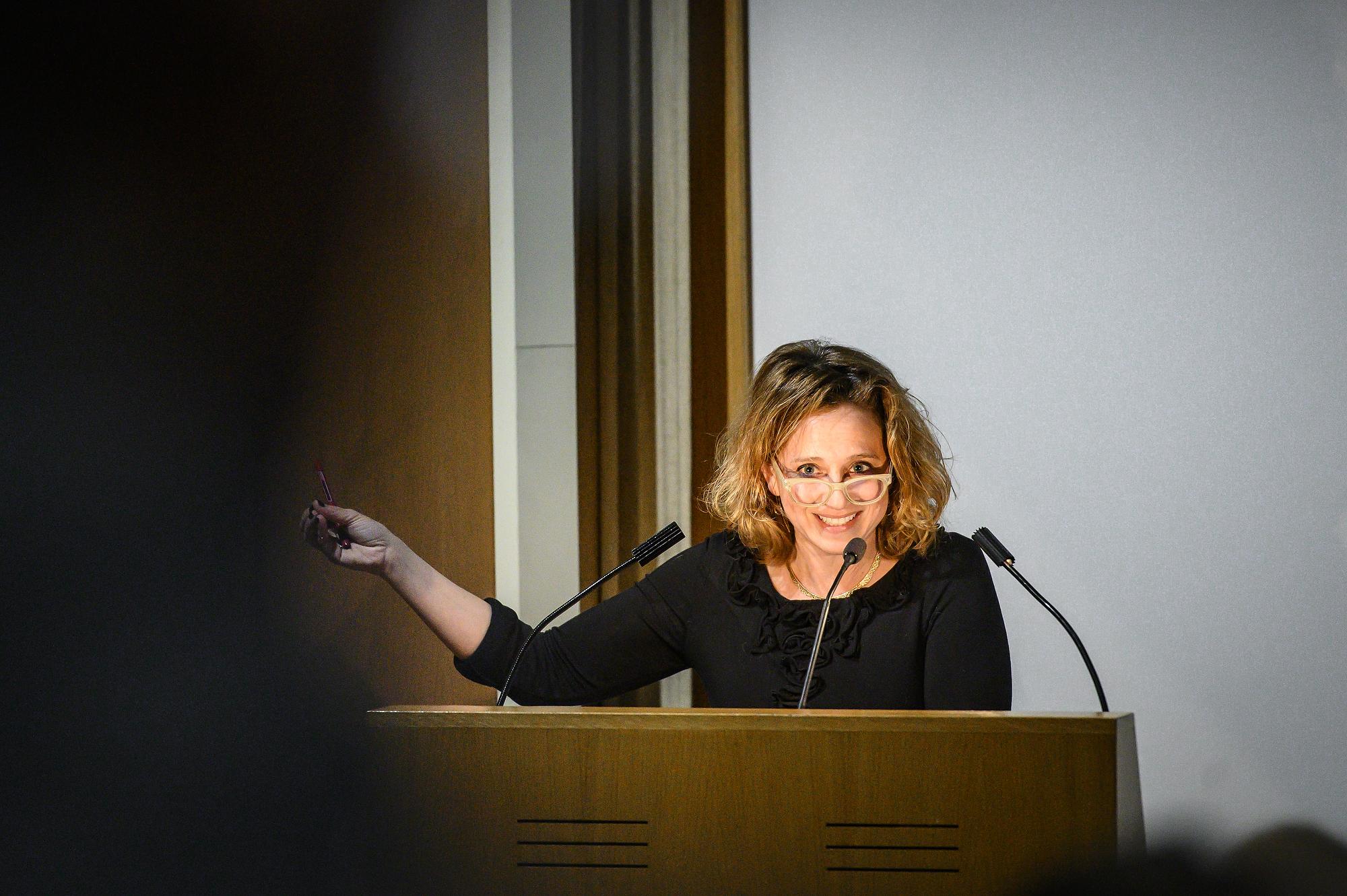 Jennifer Ratner-Rosenhagen standing behind a podium, speaking into 3 microphones