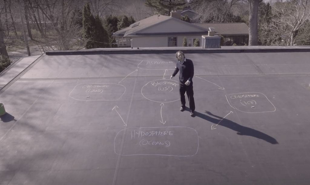 A professor stands on a chalked rooftop to teach his class.