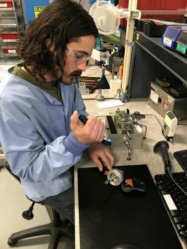 A man working with electronics at a desk.
