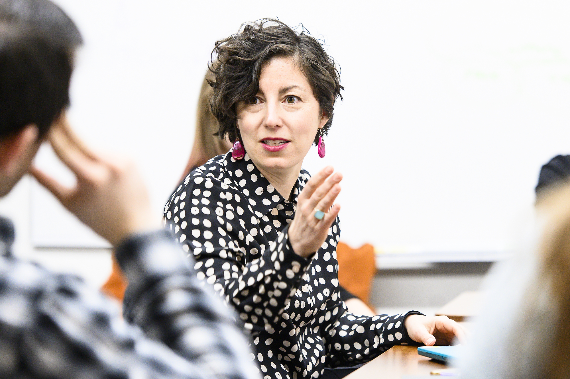 Kate Vieira sitting at a table talking to a student and gesturing with her hand