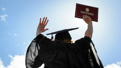 Person in cap and gown raising hands and holding diploma