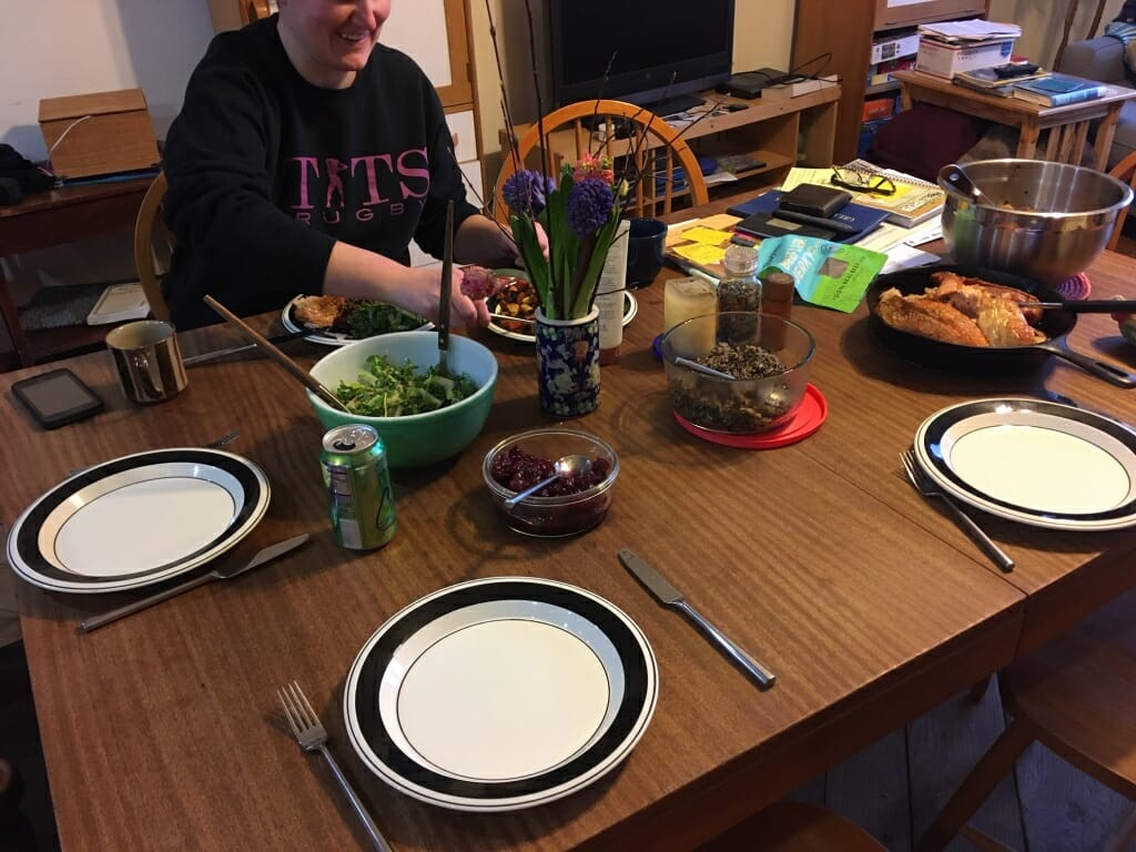 Person placing plate of food on dining table
