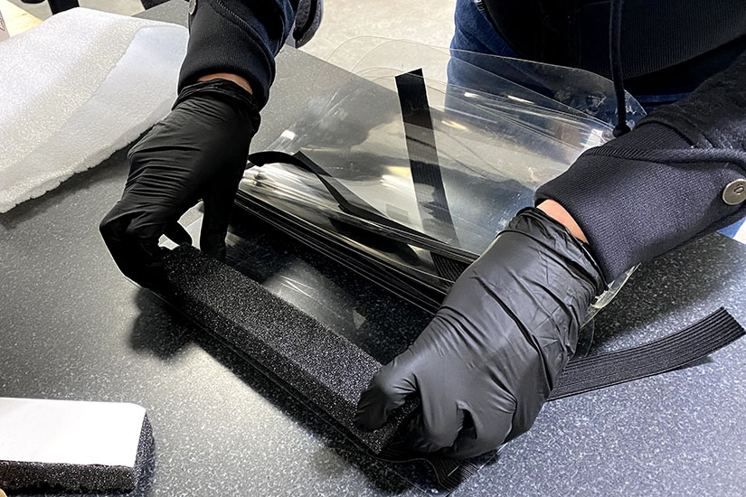 Closeup of a person's gloved hands stretching a piece of foam onto a clear plastic mask