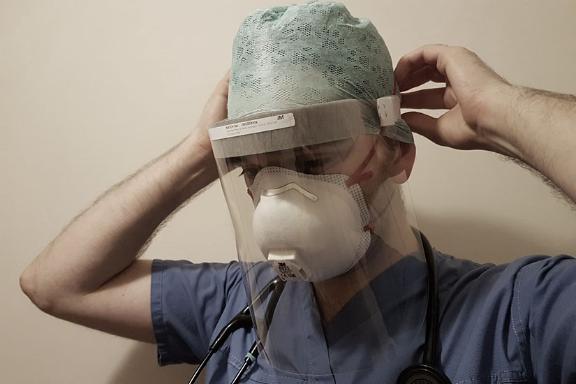 A person in scrubs with a stethoscope around their neck, fastening a clear plastic face mask behind their head