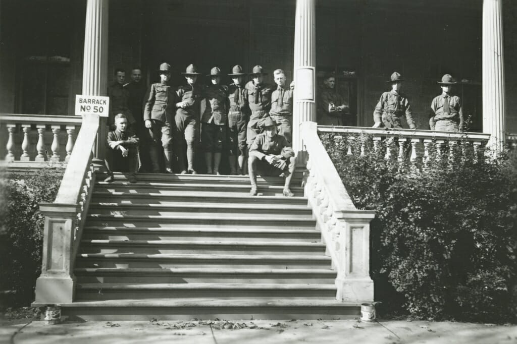 A small group of men in military uniforms standing at the top of the steps to a building