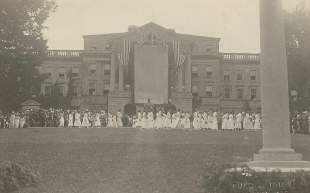 A large group of women in white dresses standing in front of Bascom Hall with a large banner and American flags