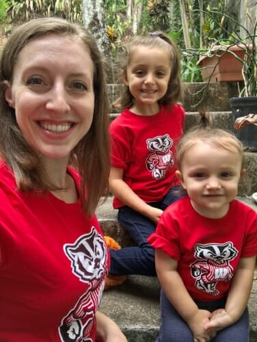 Photo of Garnier and her two young daughters all wearing Bucky Badger T-shirts
