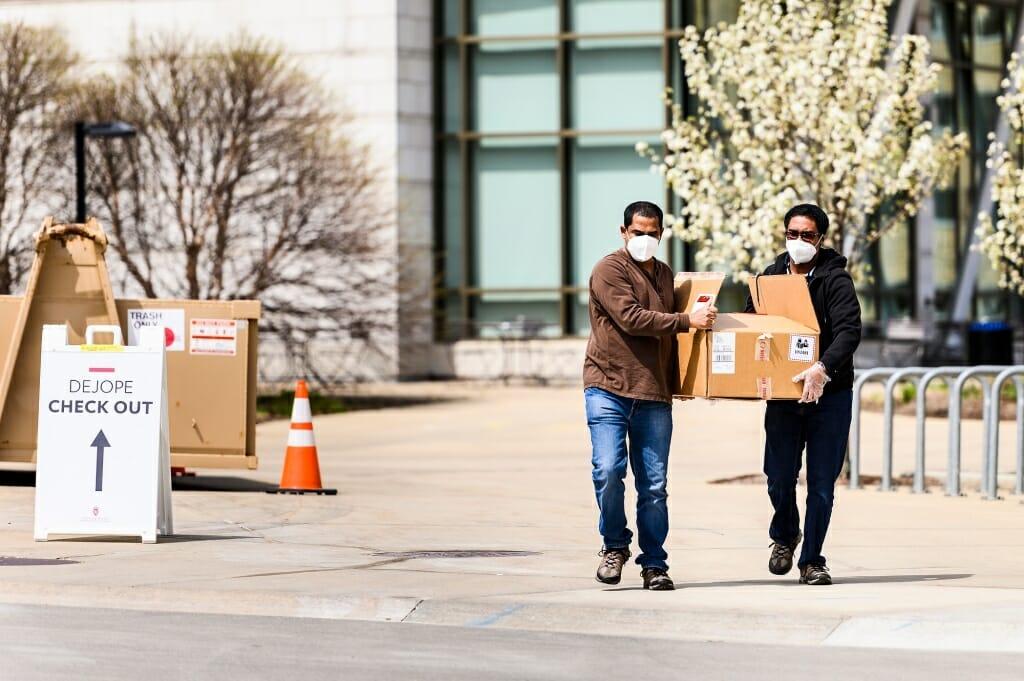 Two men walk down a campus sidewalk carrying things.