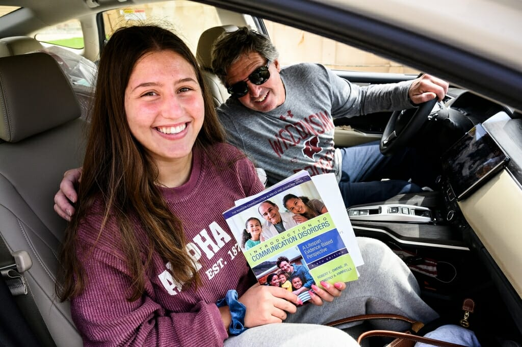 A father and daughter smile out the window of their car.