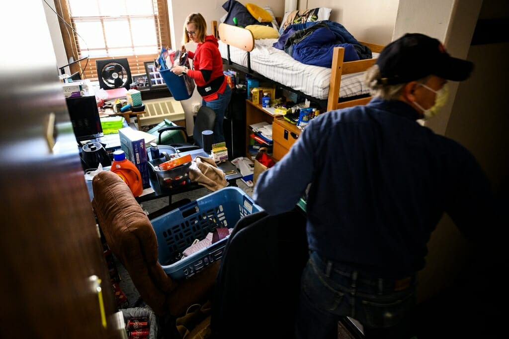 Two people pick up things in a crowded residence hall room.