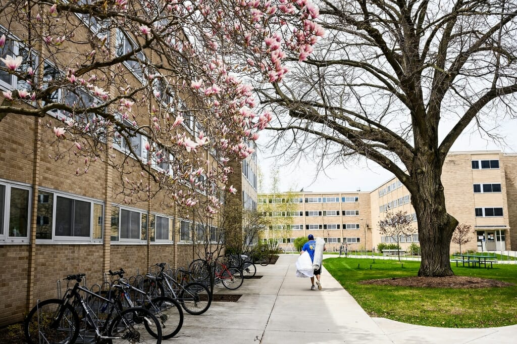 A man carries a carpet and more from a student's room in Cole Residence Hall.