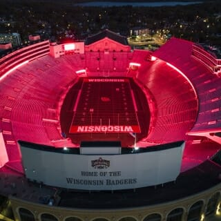 An aerial image made from a drone shows Camp Randall Stadium bathed in red light in honor of the 2020 graduating class.