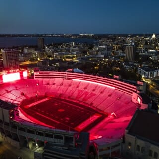 The UW Athletic Department used the stadium's scoreboard and ring display to illuminate the facility in red, shown in this photo taken from a drone.