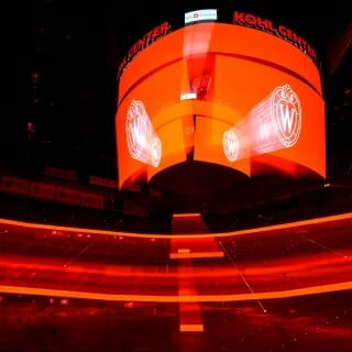 The interior arena of the Kohl Center glows in red light. The picture was made using a zoom blur during a long time-exposure.