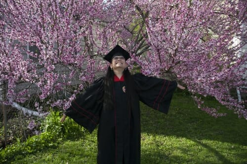 Photo of Laura Yin in her cap and gown in front of a blossoming tree